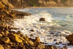 Skumma v?gen som bryter p? soluppg?ng med stenig shoreline fotografering för bildbyråer