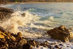 Skumma v?gen som bryter p? soluppg?ng med stenig shoreline arkivbilder