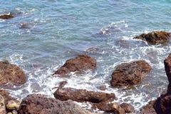 Skumma vatten på Rocky Sea Shore - naturlig bakgrund Arkivfoton