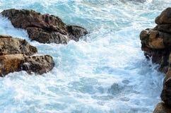 Skummande flöden för havsvatten till och med stenarna royaltyfria foton