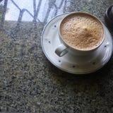 Skummande kaffe på stengolv Royaltyfria Bilder