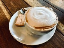 Skummande kopp kaffecappuccino med kakan på träyttersida som tjänas som på restaurangen royaltyfri fotografi