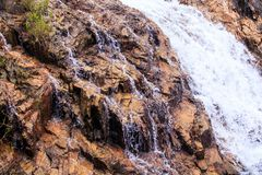 Skummande stormig snabb ström för Closeup bland bruna stenar Royaltyfri Bild