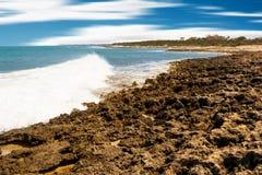 Skummande vågor som bryter på den steniga Apulian kusten och det blåa havet arkivfoton