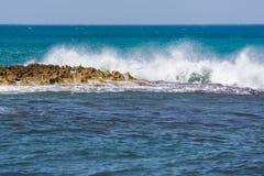 Skummande vågor som bryter på den steniga kusten och det blåa havet fotografering för bildbyråer