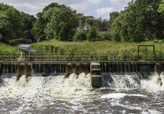 Skummande vatten som flödar till och med slussen Royaltyfri Bild