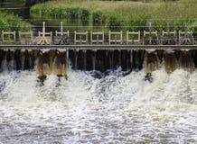 Skummande vatten som flödar till och med slussslut upp Arkivfoton