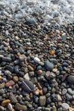 Skummar det våta ljusa skinande kulöra kiselstenstenar och havet för lodlinje arkivbild