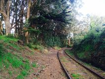 Train tracks next to a cemetery. The skunk train in fort bragg has tracks that run right through a forest my cemetery Royalty Free Stock Photo