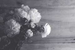 Skupiać się grupy plastikowy kwiat w wazie na drewnianym nawierzchniowym tle obraz stock