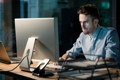 Skupiać się mężczyzna pracuje z komputerem w biurze obraz stock