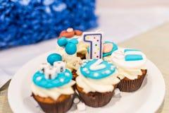 Skupia się na numerowy jeden w białą i błękitną babeczkę dla dziecka ` s urodziny Obrazy Stock
