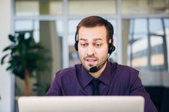 Skupia się na radosnym centrum telefoniczne agencie z jego słuchawki Zdjęcie Stock