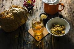 Skupia się punkt chryzantemy herbaty i wysuszonej chryzantemy na starym drewnianym stole Zdjęcia Royalty Free
