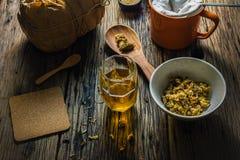 Skupia się punkt chryzantemy herbaty i wysuszonej chryzantemy na starym drewnianym stole Fotografia Stock