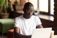 Skupiający się czarny millennial facet pracuje na komputerze obraz royalty free