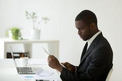 Skupiająca się amerykanin afrykańskiego pochodzenia czytanie otrzymywająca papierkowa robota zdjęcia royalty free