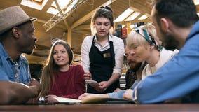 Skupiająca się atrakcyjna kelnerka zauważa rozkaz notatnik od firmy modnisiów przyjaciele w barze, pub zdjęcie wideo
