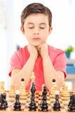 Skupiająca się chłopiec bawić się szachy sadzającego przy stołem indoors Obraz Stock