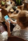 Skupiająca się dama w pasiastej kurtki odbiorczej wiadomości na jej smartphone fotografia stock