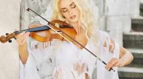Skupiająca się kobieta bawić się skrzypce Zdjęcia Royalty Free