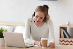 Skupiająca się kobieta w słuchawki używać laptop, pisze notatkach obraz royalty free