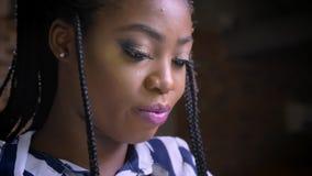 Skupiająca się twarz afrykańska dziewczyna koncentrował na typying na jej pastylce podczas gdy siedzący przy stołem nad ściana z