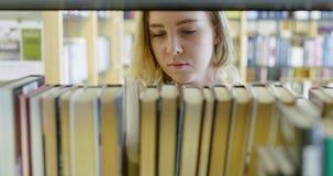 Skupiający się żeński uczeń wybiera książkę w szkolnej bibliotece zdjęcie wideo