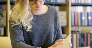 Skupiający się żeński uczeń z szkła działaniem w szkolnej bibliotece zbiory wideo