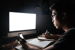 Skupiający się azjatykci mężczyzna używa pustego ekranu komputer i telefon komórkowego Zdjęcie Royalty Free