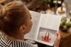 Skupiający się blondynka klient attentively czyta artykuł na ciekawym temacie obrazy royalty free