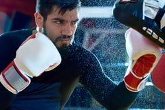 Skupiający się bokser uderza pięścią ochraniaczów fotografia royalty free