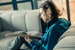 Skupiający się ciemnowłosy mężczyzna z ściernią pokojowo bawić się na gitarze obraz stock