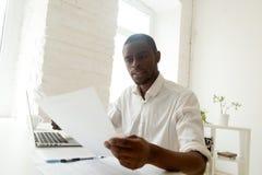 Skupiający się czarny pracownik analizuje firm statystyki czyta papiery obrazy stock