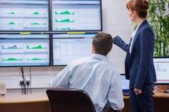 Skupiający się koledzy analizuje rezultat na ich komputerze Zdjęcia Stock