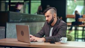 Skupiający się młody freelancer mężczyzna siedzi przy jawnym cukiernianym miejscem z modną fryzurą pracuje na laptopu komputerze  zbiory wideo