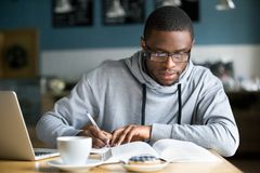 Skupiający się millennial afrykański uczeń robi notatkom podczas gdy studiujący i obrazy royalty free