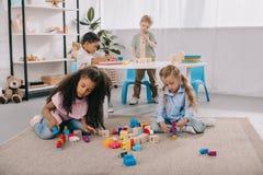 skupiający się multiracial preschoolers bawić się z drewnianymi blokami fotografia stock
