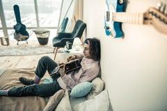 Skupiający się niezwykły młody człowiek odpoczywa w sypialni z gitarą obrazy royalty free