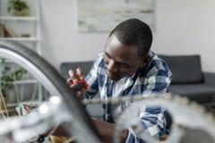 skupiający się przystojny afro mężczyzny naprawiania bicykl zdjęcia stock