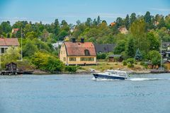A private motorboat passing by houses on Skurusundet river. SKURUSUNDET RIVER, SWEDEN - July 11, 2018 : A private motorboat passing by houses on Skurusundet royalty free stock images