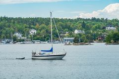 A private sailboat towing a dinghy on Skurusundet river. SKURUSUNDET RIVER, SWEDEN - July 11, 2018 : A private sailboat towing a dinghy on Skurusundet river stock photography