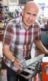 Skuteczny starszy mężczyzna robi pojazd liczbom na maszynie Fotografia Royalty Free
