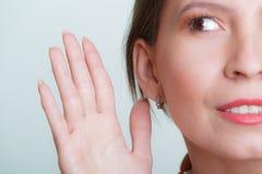 Skvallerflickatjuvlyssnande med handen som gå i ax Arkivfoton