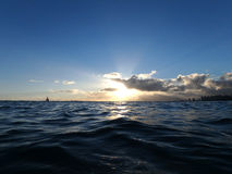 Skvalpar ljusa sken för solnedgång till och med molnen som vågor på nollan Arkivbild