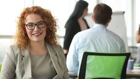 Skwaśniały bizneswoman patrzeje ar kamerę na frontowym widoku, ono uśmiecha się zdjęcie wideo