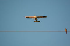 In the sky. Aeroplane flying over power line with a bird on Stock Photo