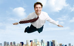 In the sky. Conceptual image of smiling businessman flying in the clouds Stock Photos