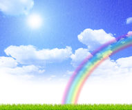 Sky. Green grass over a blue sky background with rainbow Stock Image