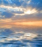 Sky. With a visible sun rays and rippled water royalty free stock image